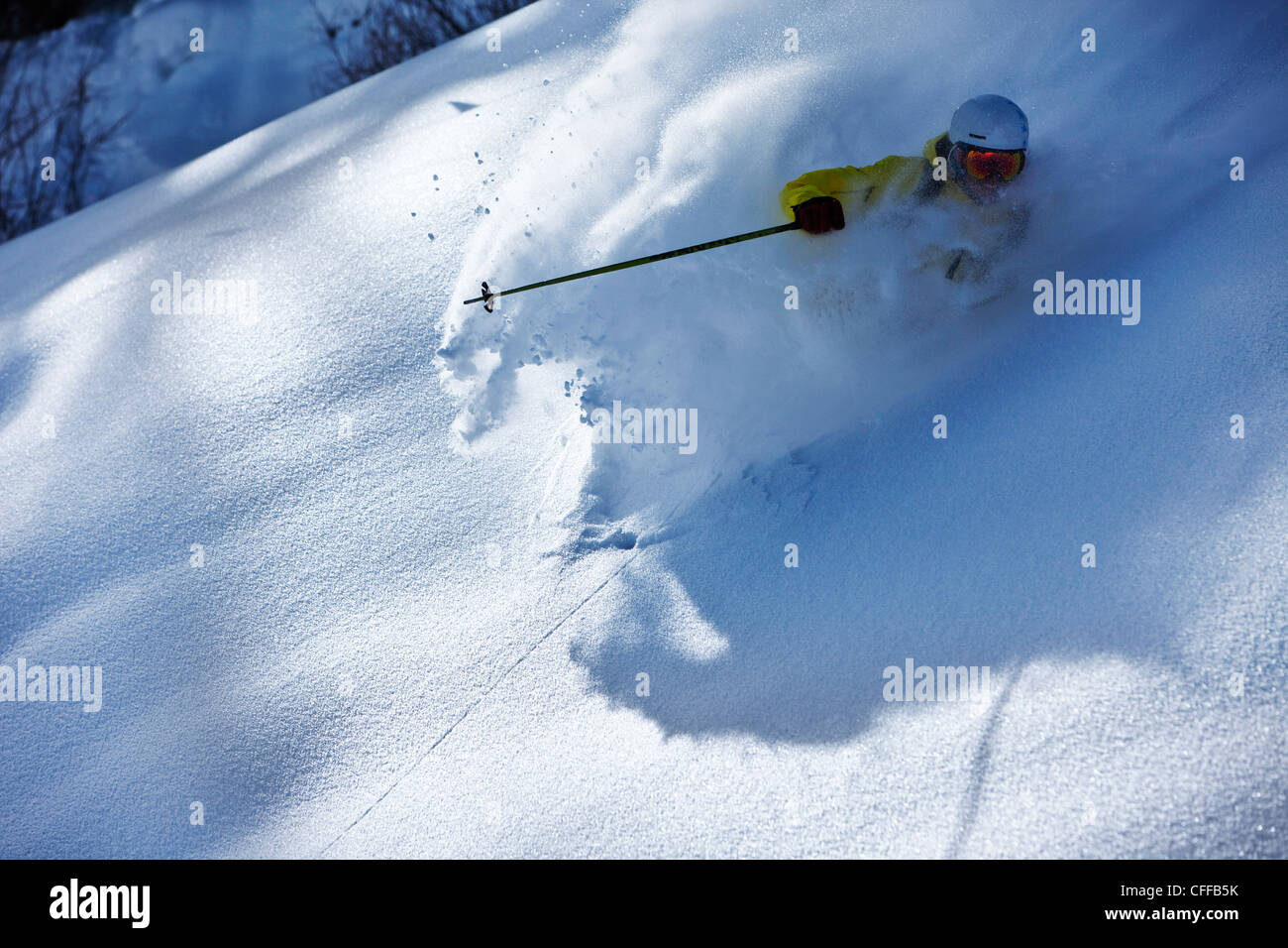 A athletic skier rips fresh powder turns on a sunny day in Colorado. - Stock Image
