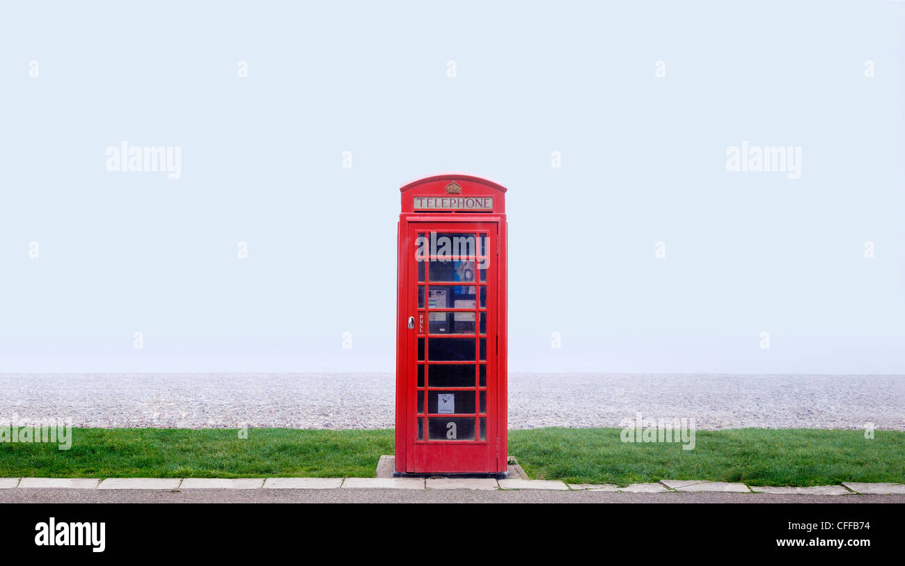Red telephone box on a grass strip in front of a misty beach scene - Stock Image