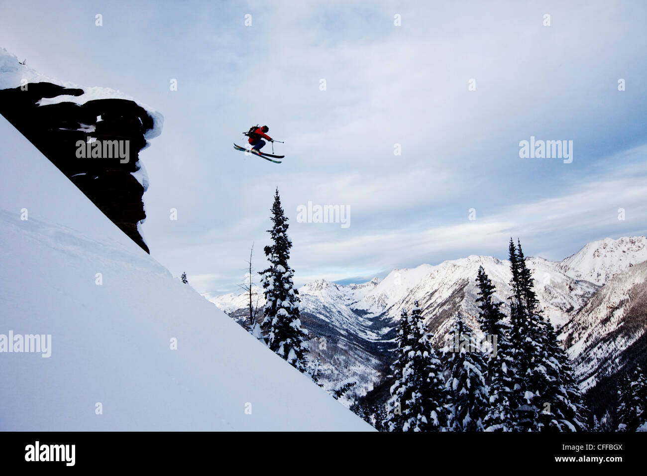A athletic skier jumping off a cliff in the backcountry in Colorado. - Stock Image