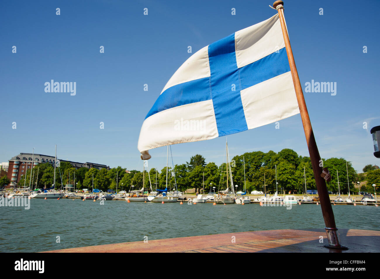 The Finnish flag flies from a boat shuttling between Unisaari island and the Merisatama quayside, Helsinki Finland Stock Photo