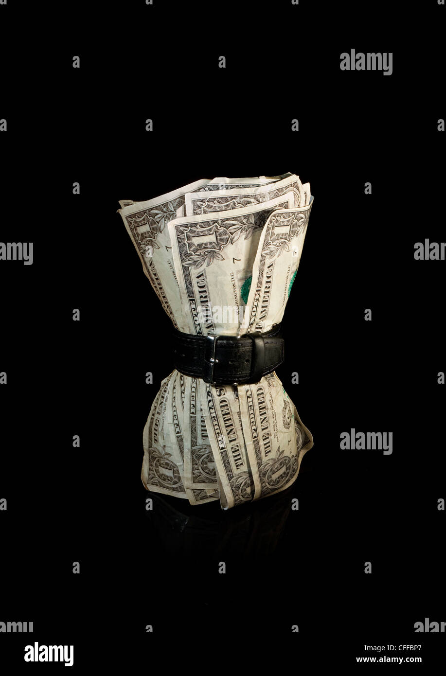 Dollar bills squeezed by belt symbolizing a tight economy - Stock Image