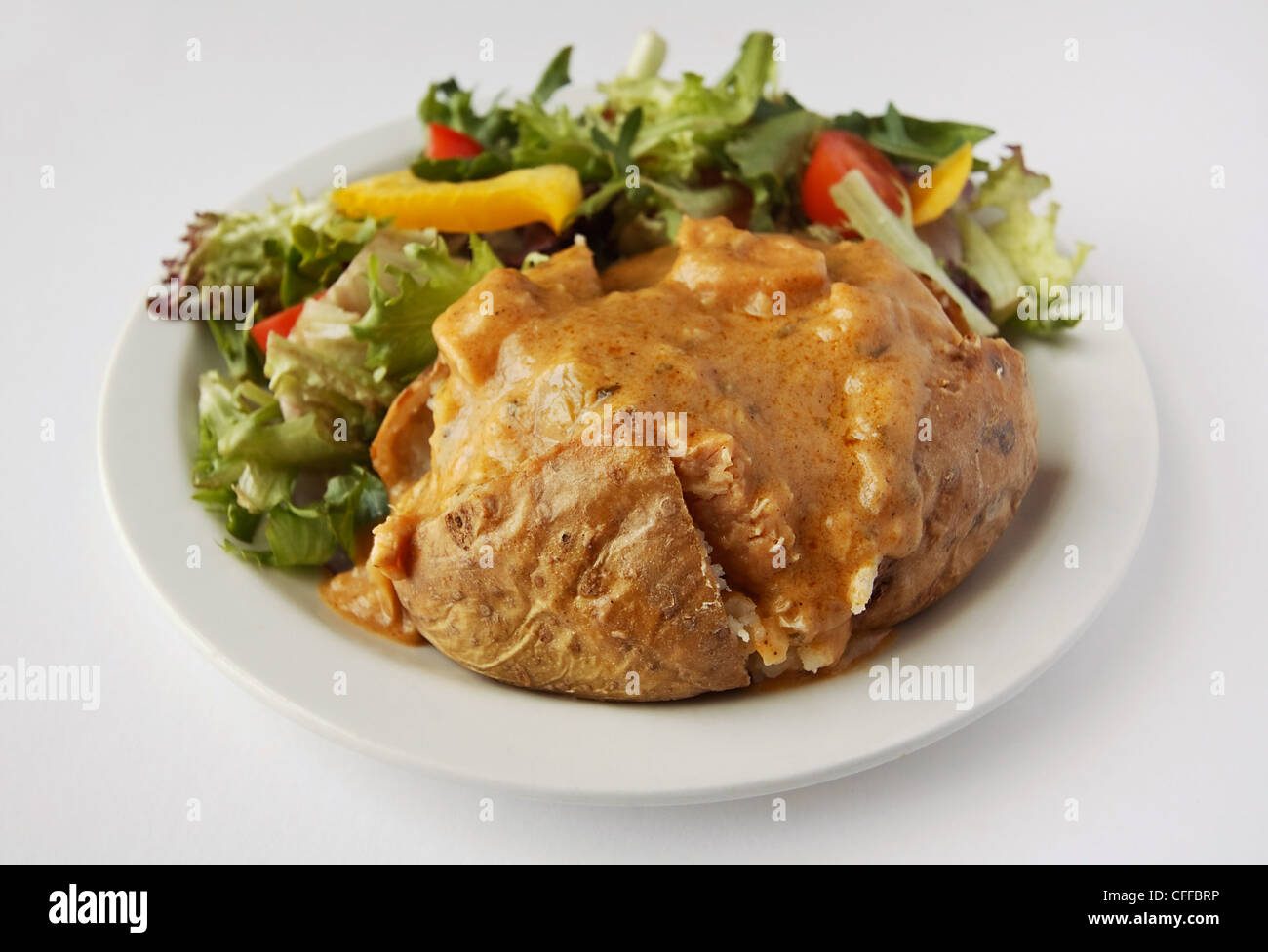 baked potato with curry filler on a plate with side salad - Stock Image