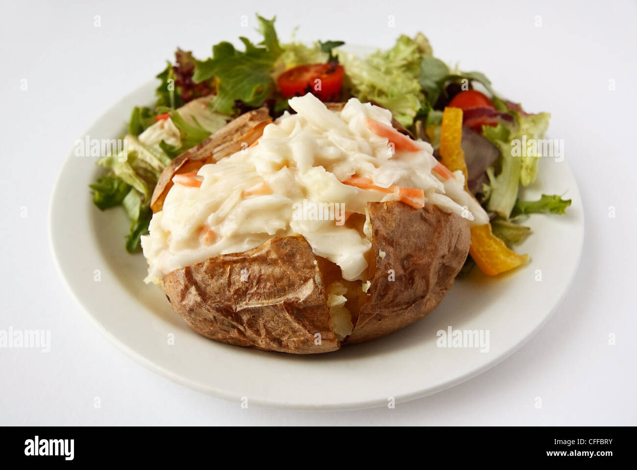 A baked potato with coleslaw filling on a plate with side salad - Stock Image