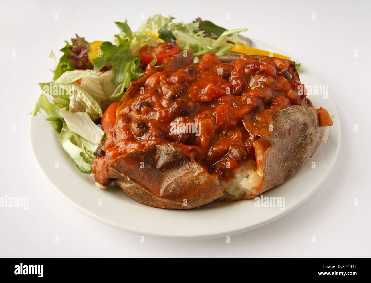 A beef chili baked potato on a plate with side salad - Stock Image