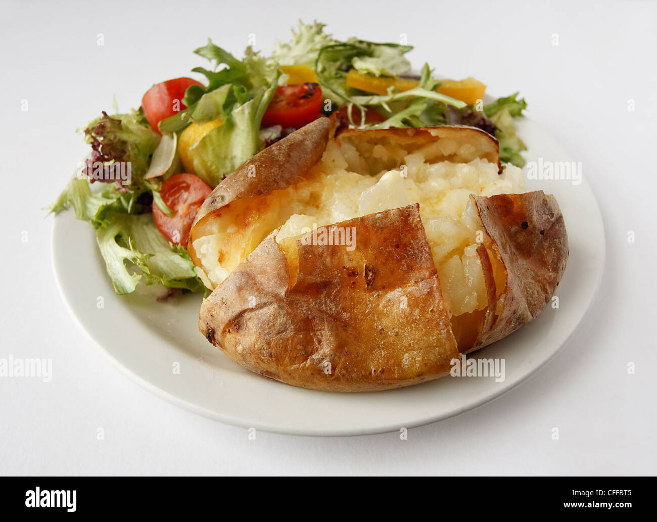 A plain butter baked potato on a plate with side salad - Stock Image