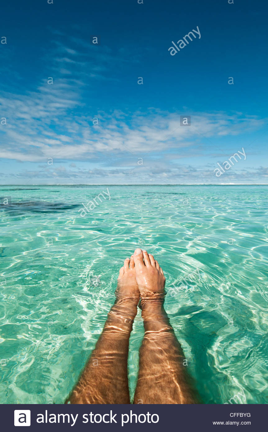 View over a man's legs and feet while floating in a lagoon, Rarotonga, Cook Islands. - Stock Image