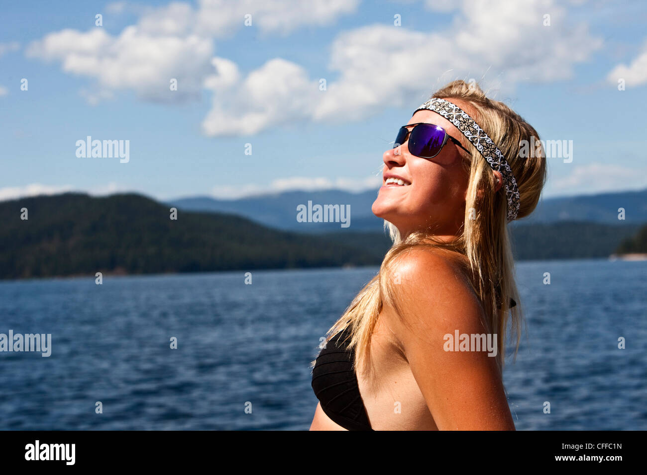 A athletic young woman smiles while subathing next to a lake in Idaho. - Stock Image