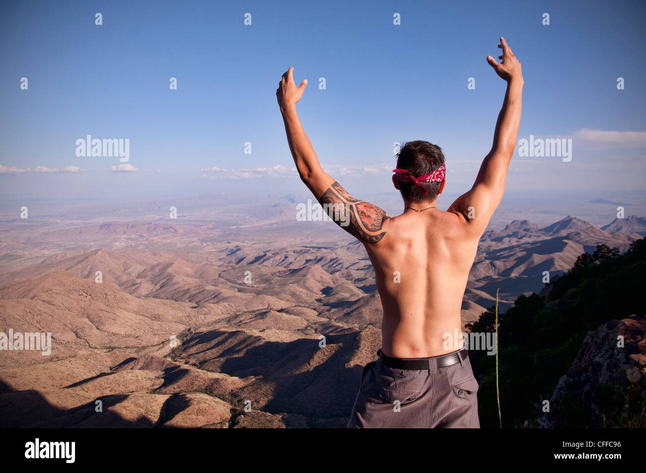 A young man celebrates at the top of The South Rim in Big Bend National Park. - Stock Image