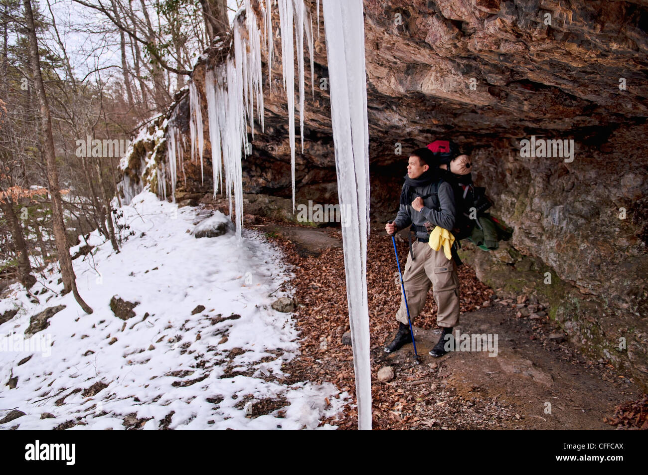 A young man rests from backpacking in the snow and ice under the cover of a rock ledge. - Stock Image