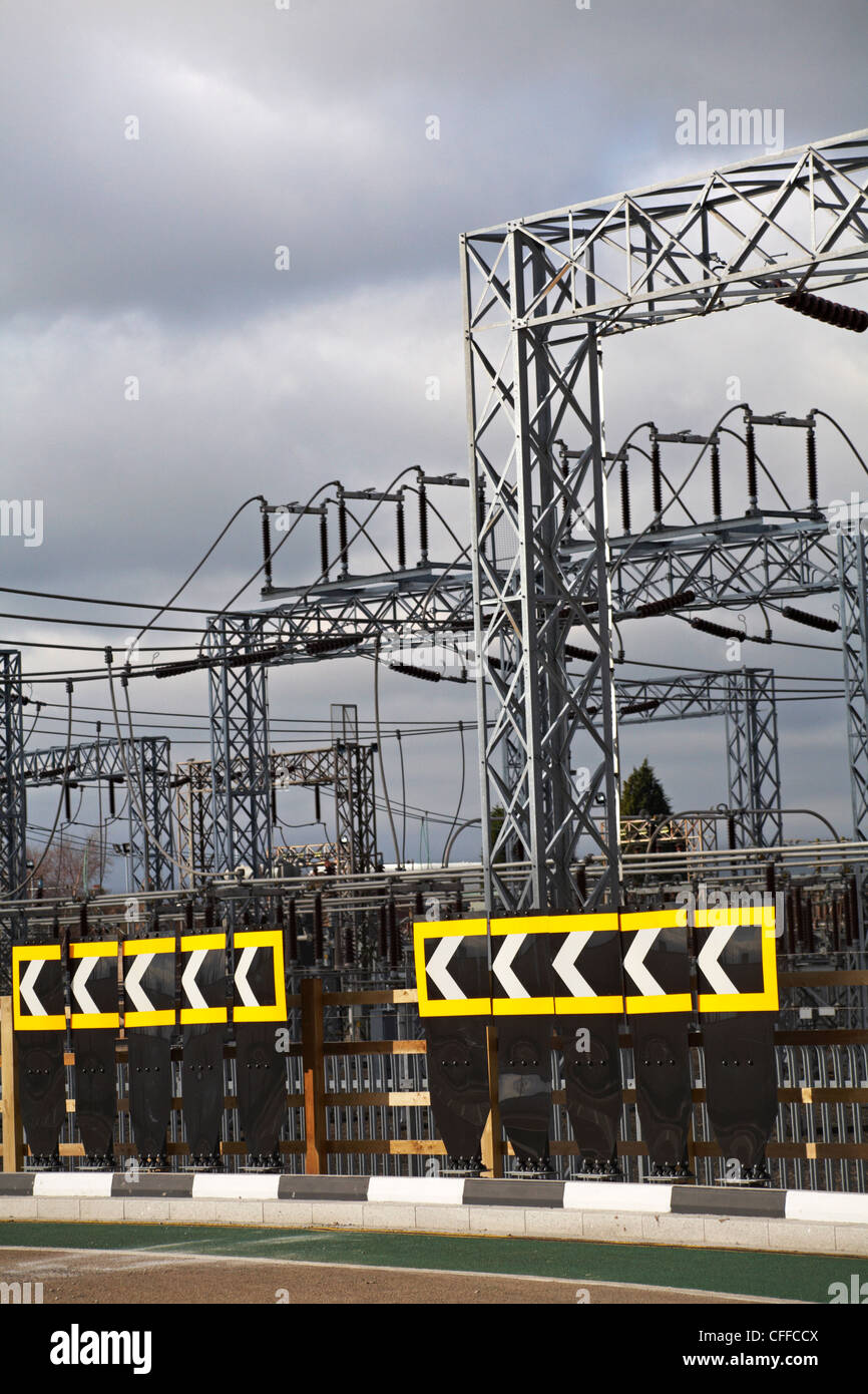 electricity grid with sharp bend road signs under grey skies at Hamworthy, Dorset in February - Stock Image
