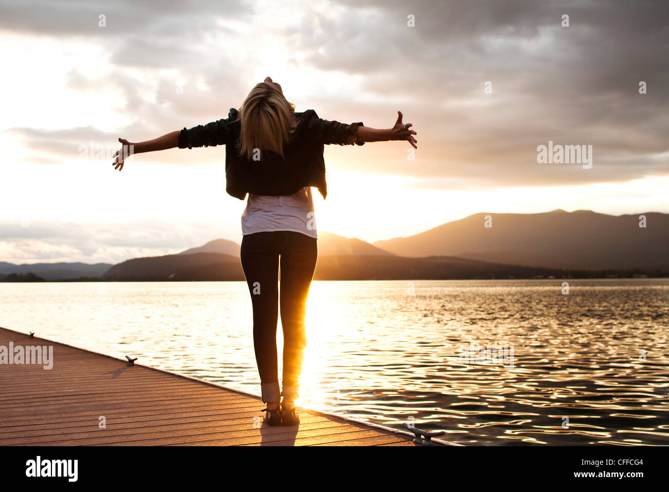 A beautiful young woman looking into the distance holds her arms out embracing the sunset over a lake in Idaho. - Stock Image