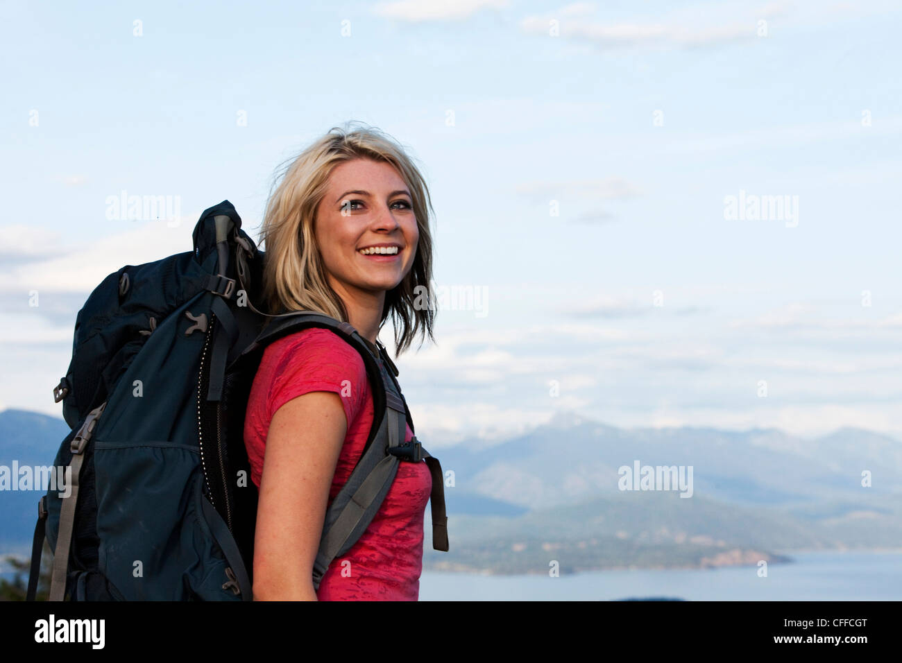 A athletic woman smiling on a backpacking trip in Idaho. - Stock Image