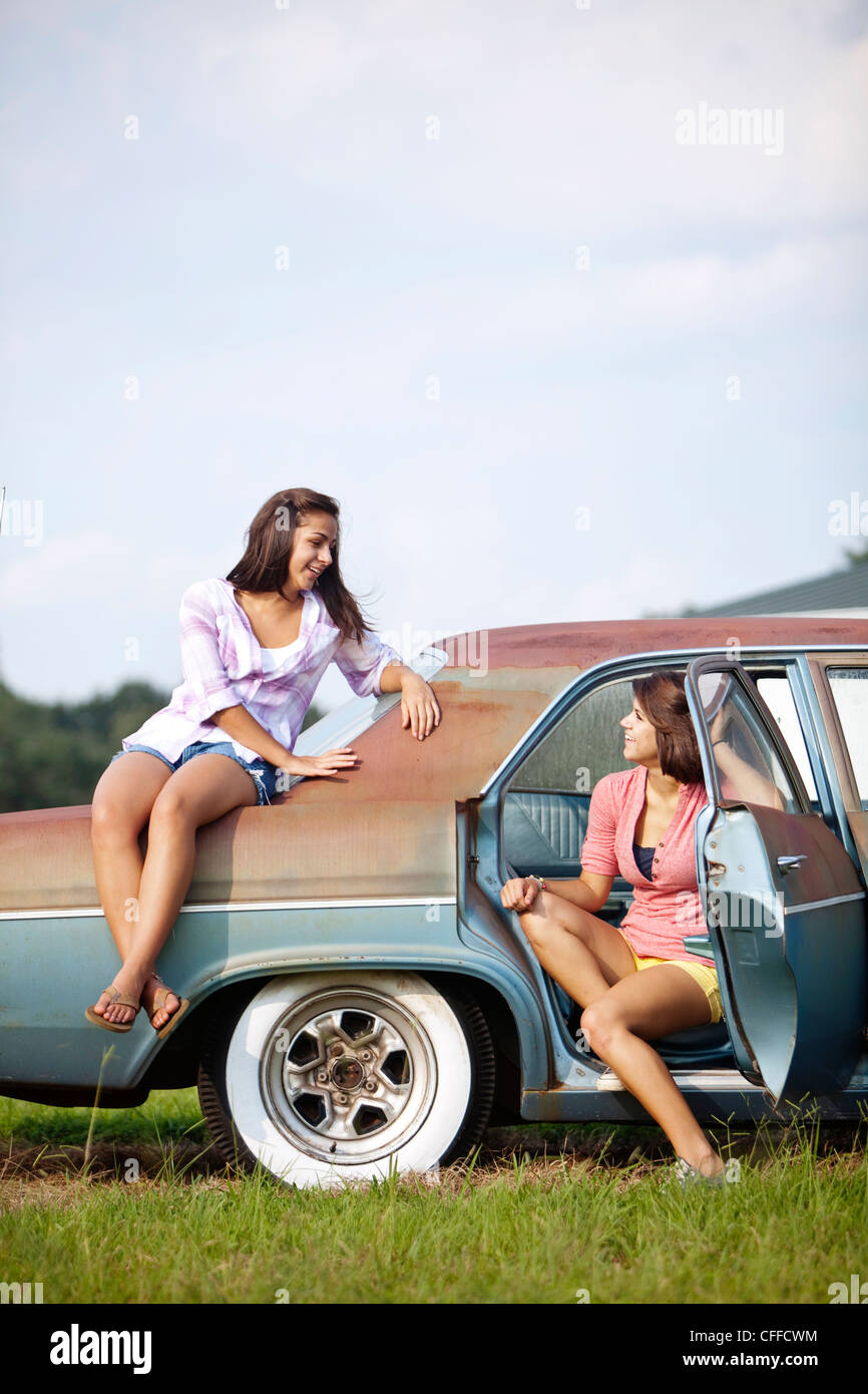Two sisters hang out on a classic car. - Stock Image