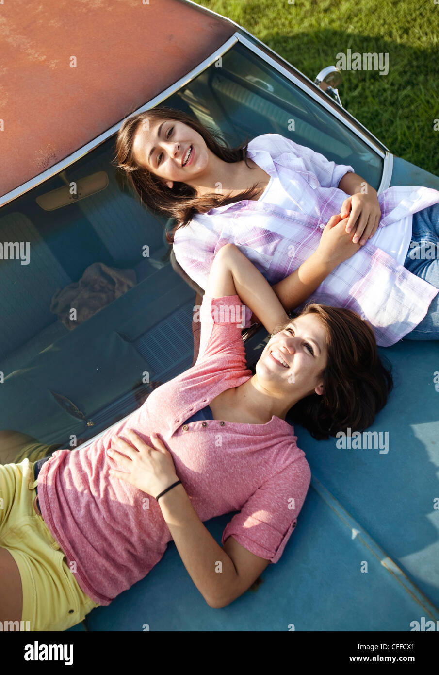 Two sisters lay  on the hood of an old car. - Stock Image