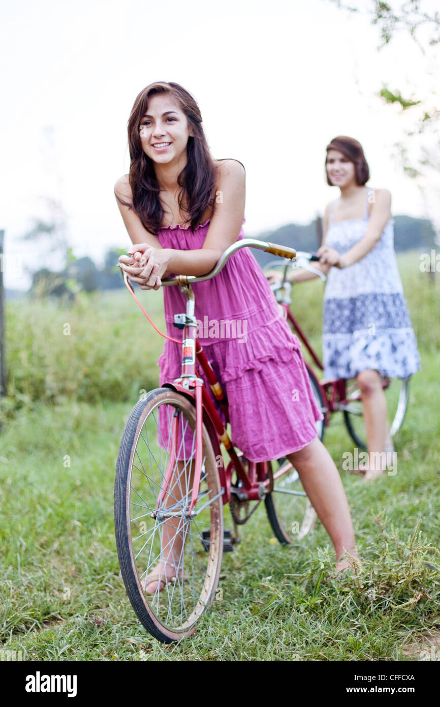 Two sisters stand with their bikes in a field. Stock Photo