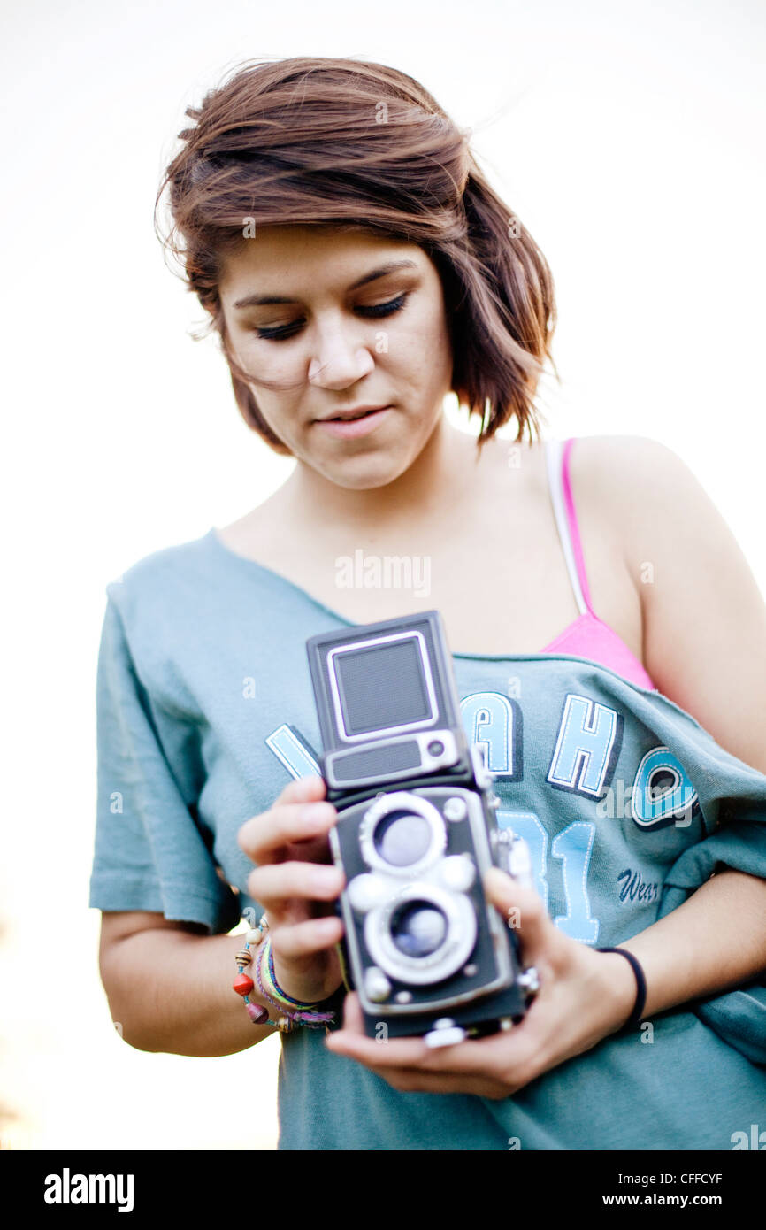 A young woman takes a photo with a classic camera. - Stock Image