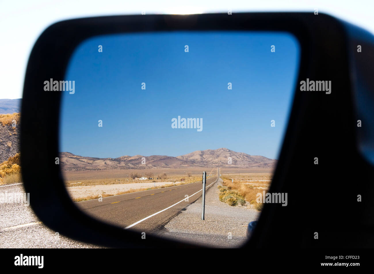 Highway 50 in Nevada, better known as the Loneliest Road in America, is reflected in a rearview mirror. - Stock Image