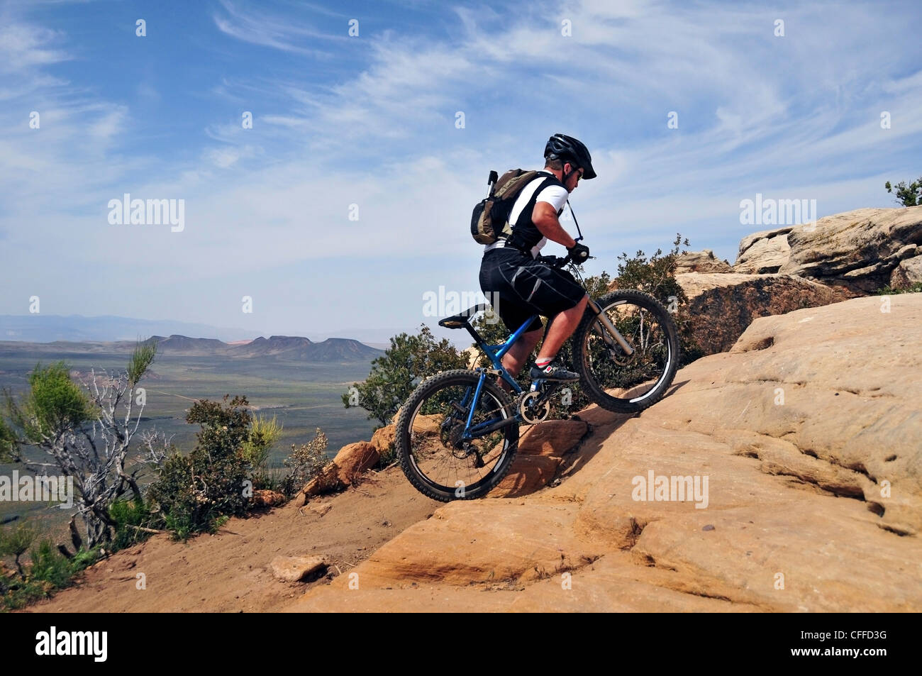 A man mountain bikes on the South Rim Trail of Gooseberry Mesa in southern Utah. - Stock Image