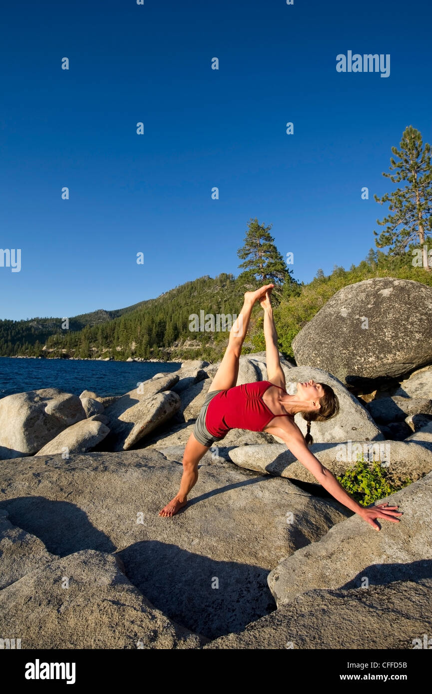 A young woman performs yoga in warm afternoon light on granite boulders on the east shore of Lake Tahoe in the summer, - Stock Image