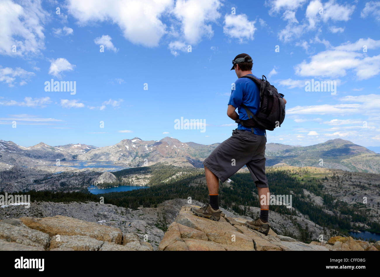 A male hiker stands on the summit of Mount Ralston looking over Desolation Wilderness in the summer, CA. - Stock Image