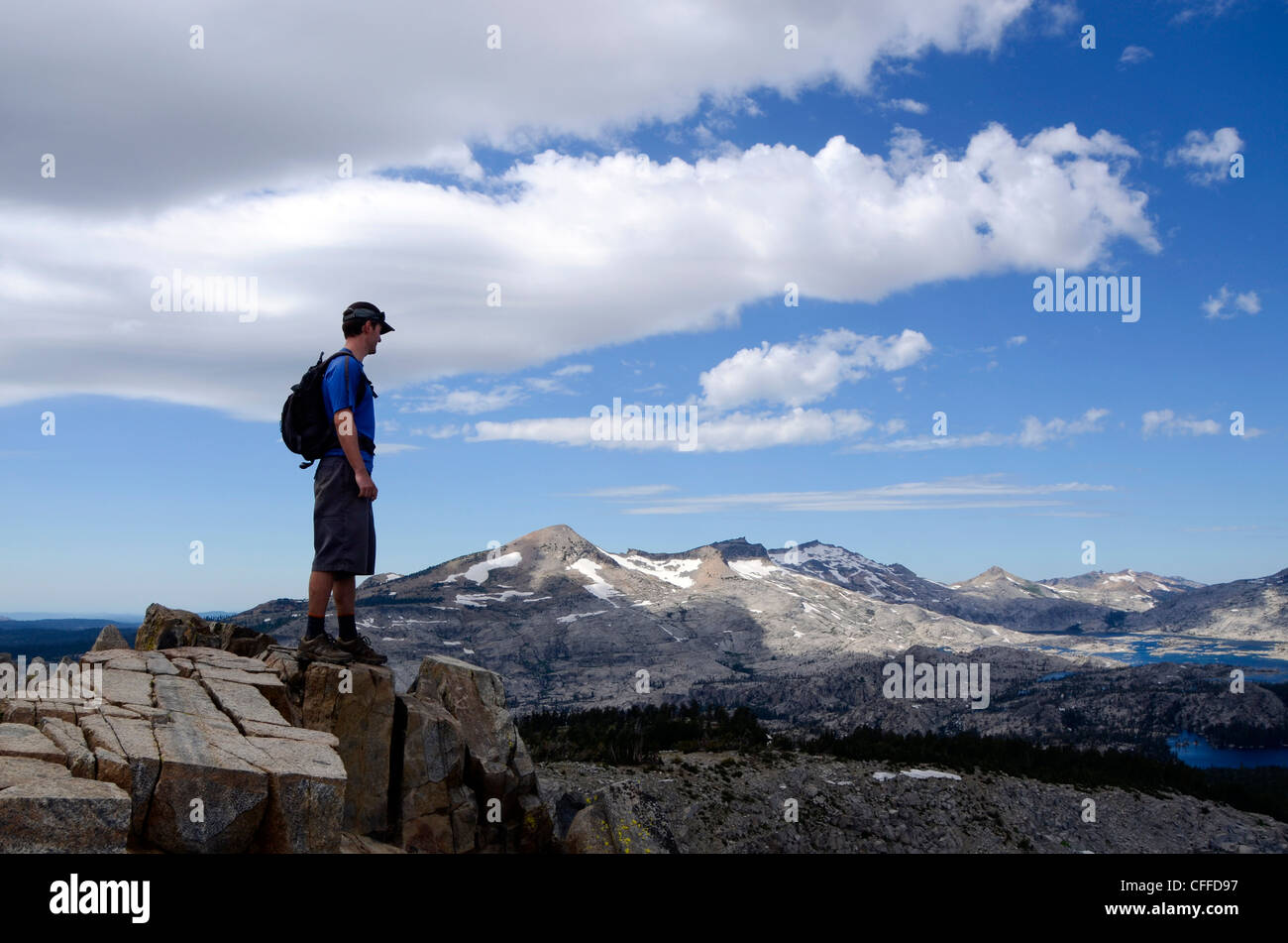 A male hiker stands on the summit of Mount Ralston looking over Pyramid Peak and Desolation Wilderness in the summer, - Stock Image