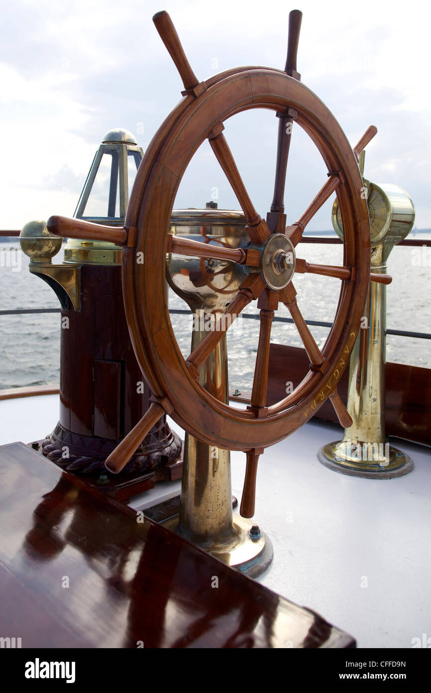 A ship's wheel and compass at the helm of a restored steamship at anchor in Maine. - Stock Image