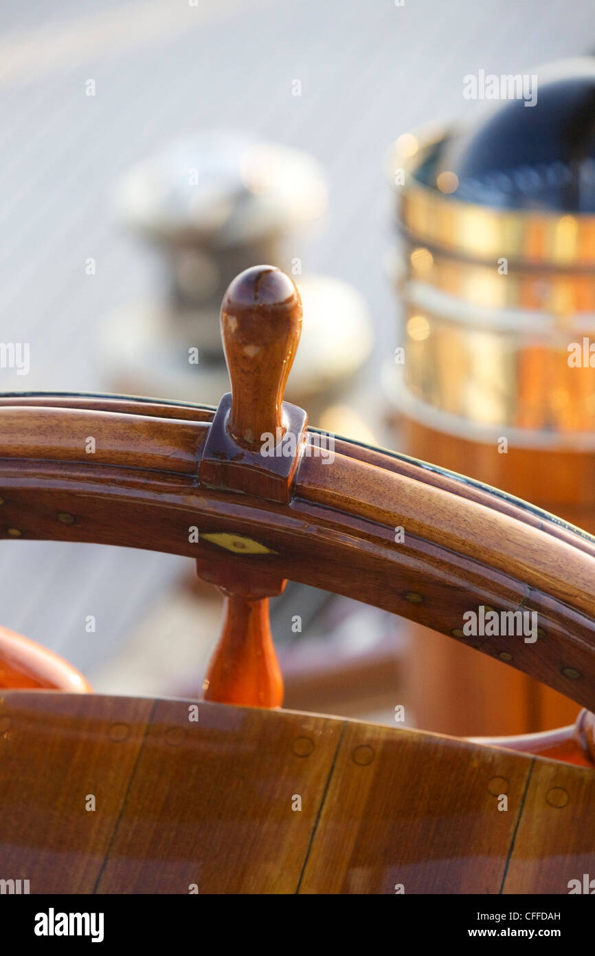 A warm glow highlights the ship's wheel on board a classic sailing yacht as sunset approaches. - Stock Image