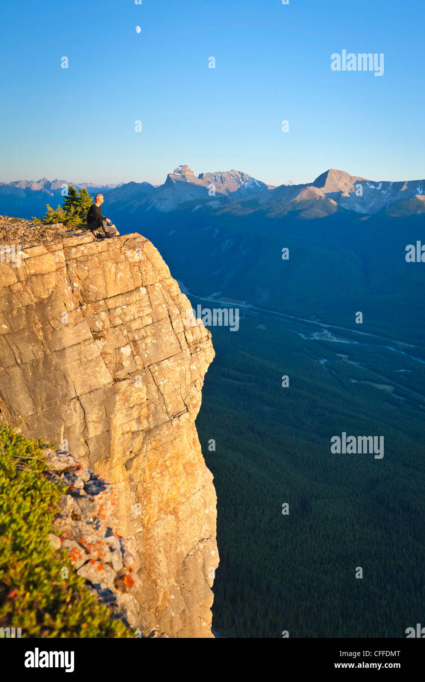 A hiker sits on a cliff edge, Banff National Park, Alberta, Canada. - Stock Image