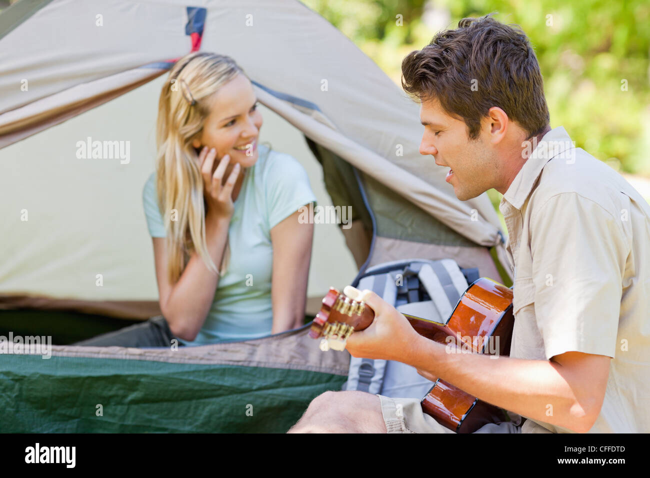 Man sings and plays guitar as his girlfriend smiles - Stock Image
