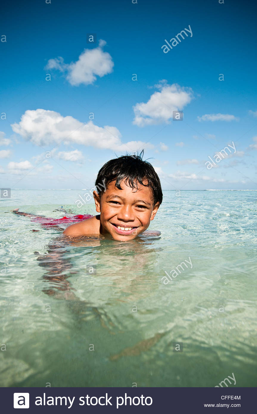 Young boy smiling at camera while swimming in a lagoon, Cook Islands. - Stock Image