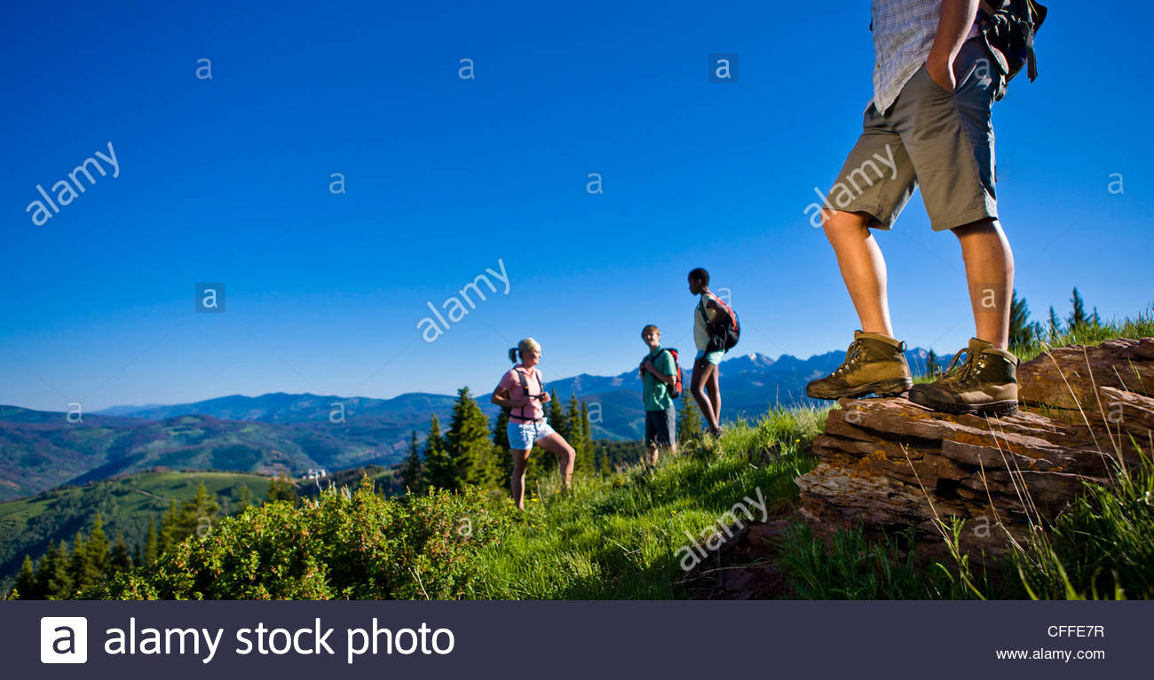 A man stands on a rock at the top of a hike, as his friends wait in the background. - Stock Image