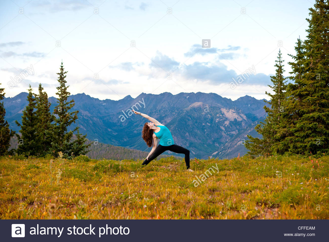 A woman performs a Hatha Yoga pose on a mountain top. - Stock Image