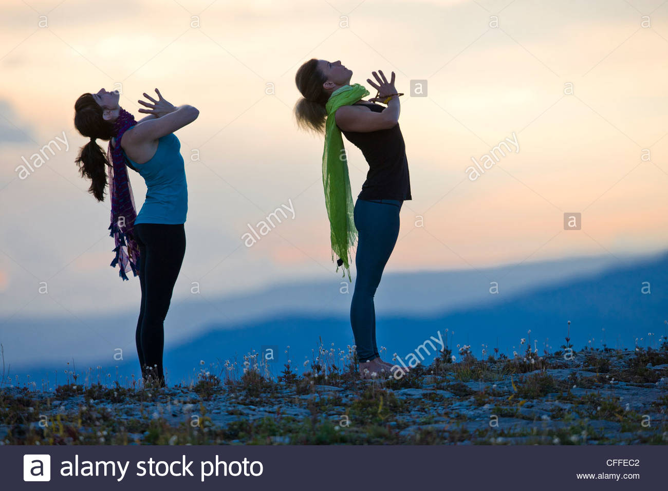 Two women perform Hatha Yoga poses on a mountain top. - Stock Image