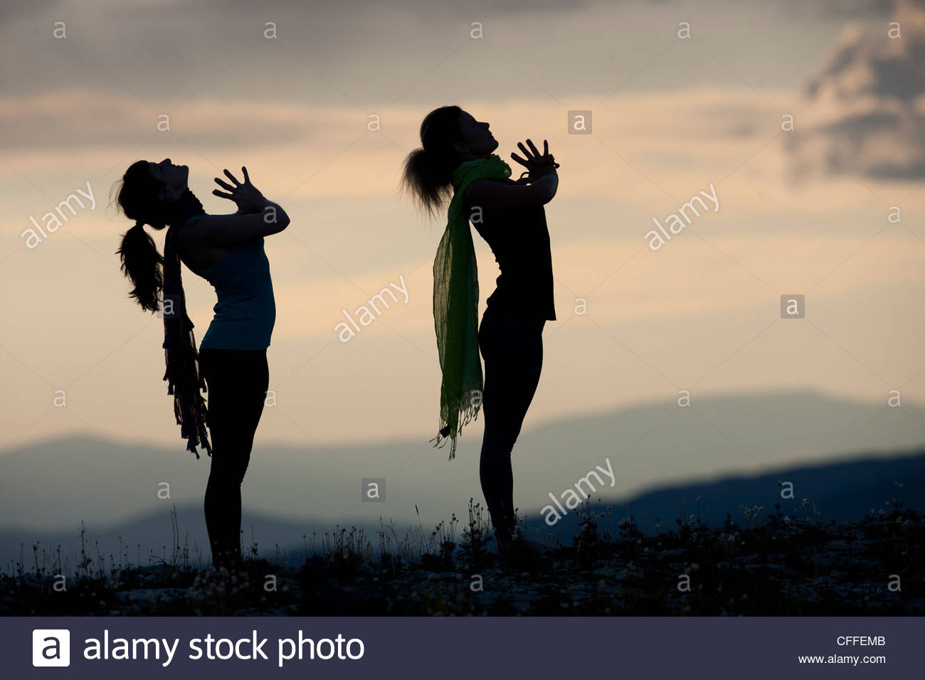 Silhouette of two people practicing yoga - Stock Image