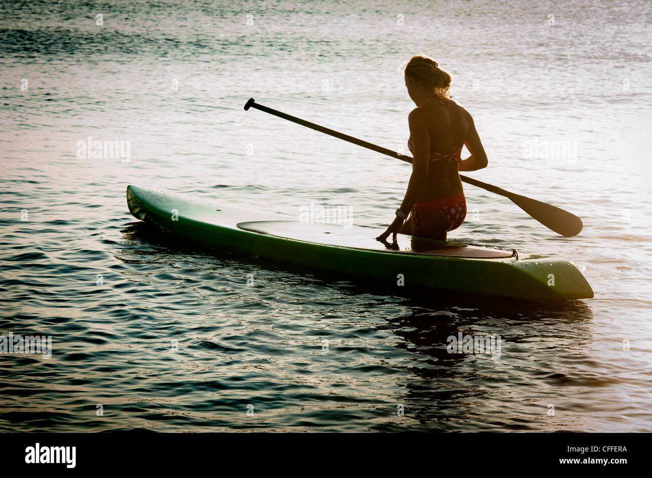 A woman enjoys her stand up paddle board. - Stock Image