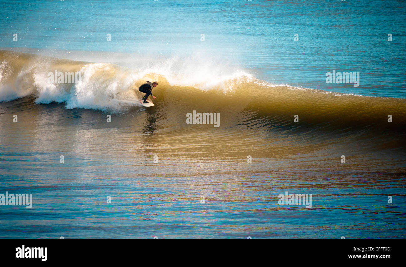 An east coast surfer rides a barrel. - Stock Image