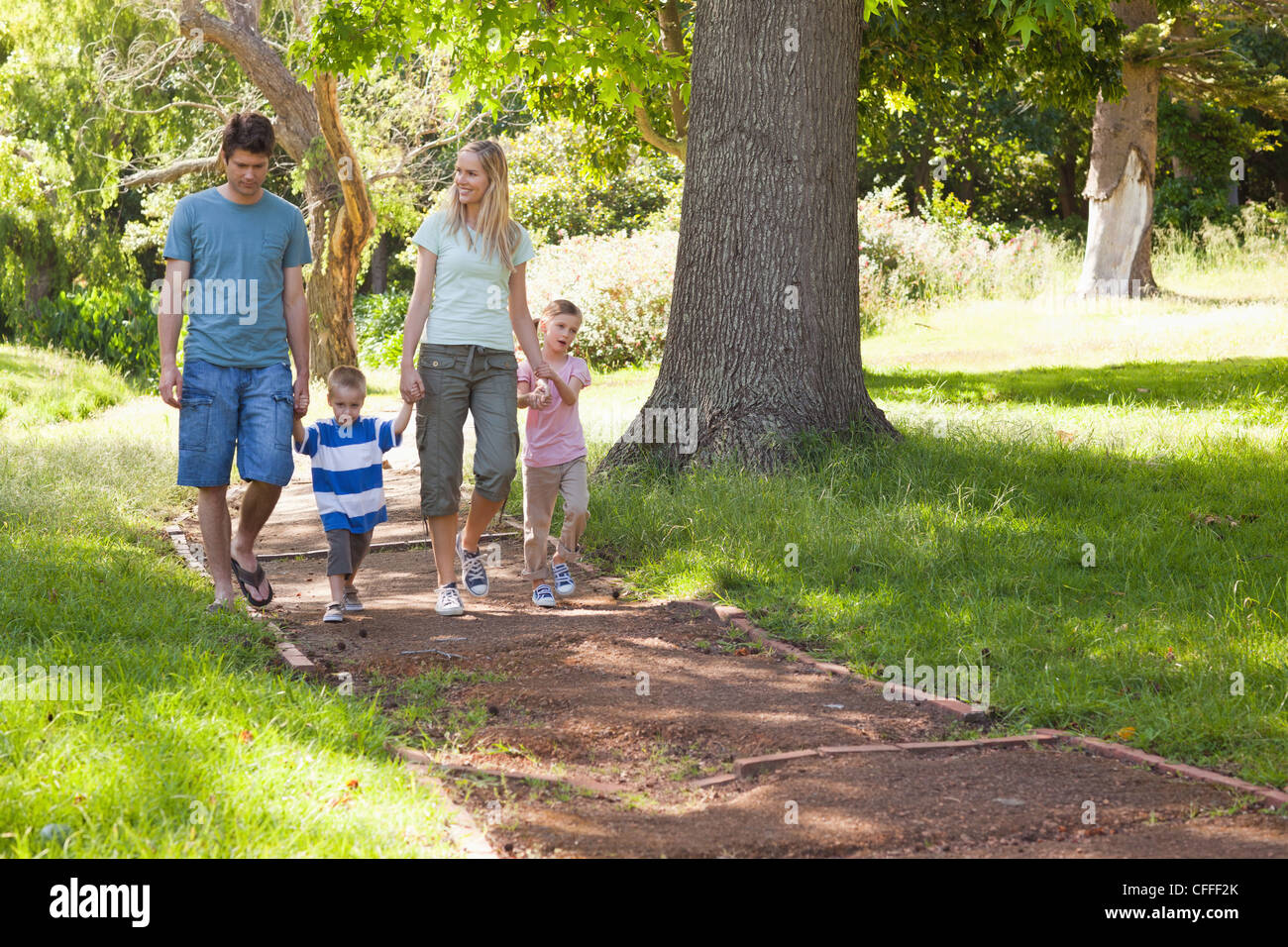 A family walking towrds the camera getting closer - Stock Image