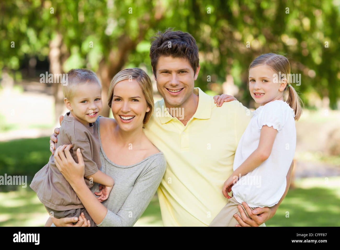 Two parents in the park carrying their kids - Stock Image