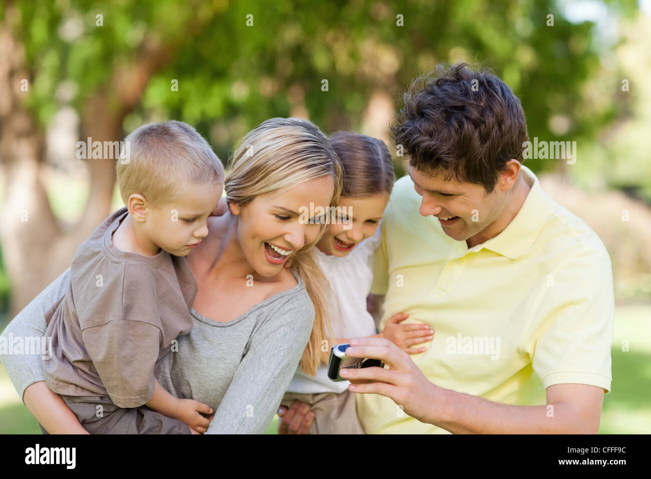 Smiling family looking at the photo they took - Stock Image