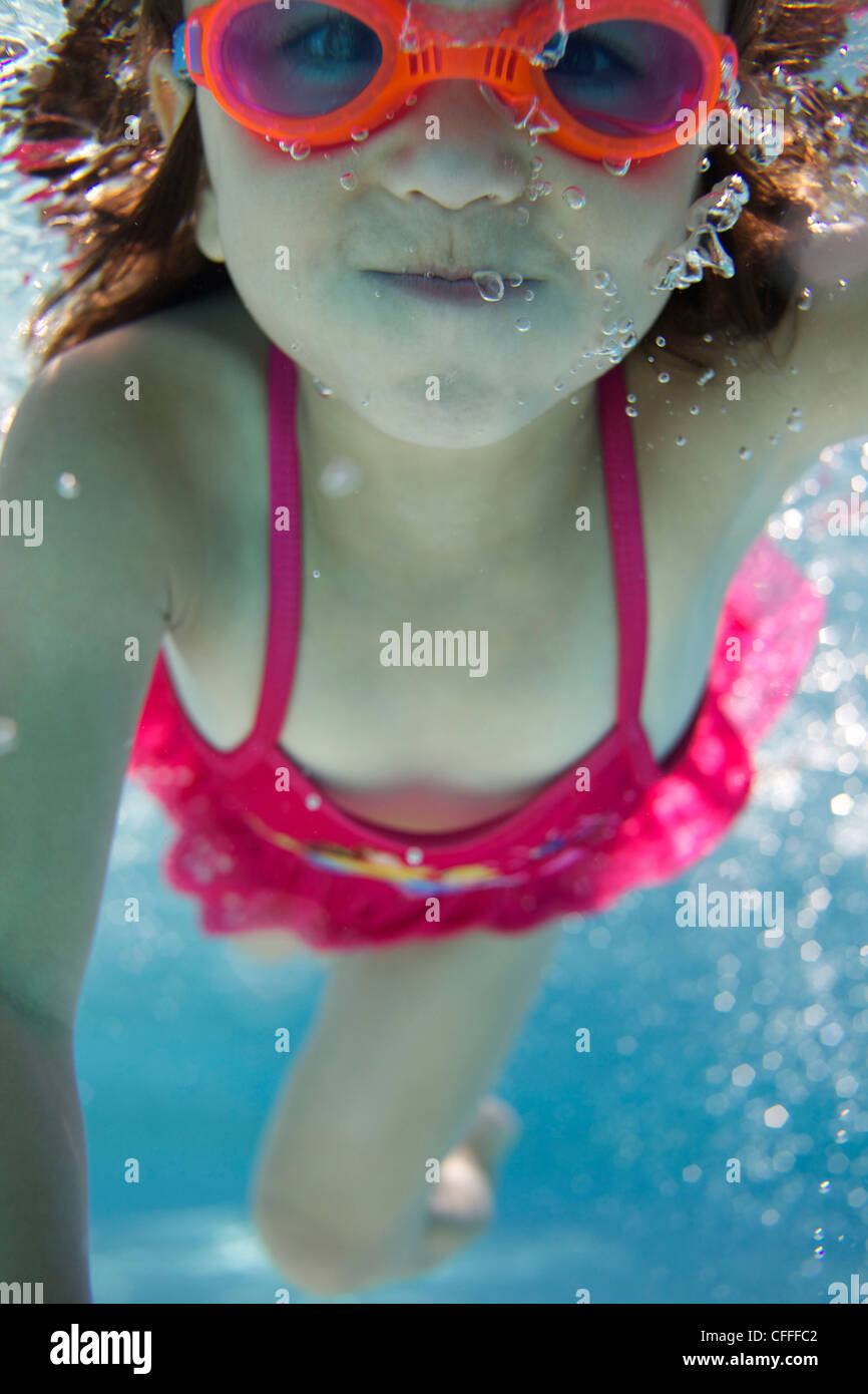 A young girl swims in a pool. - Stock Image