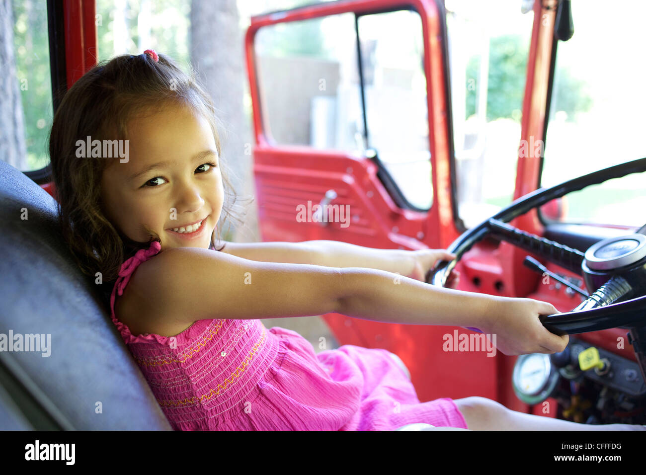 A young girl plays with the steering wheel of a car. - Stock Image