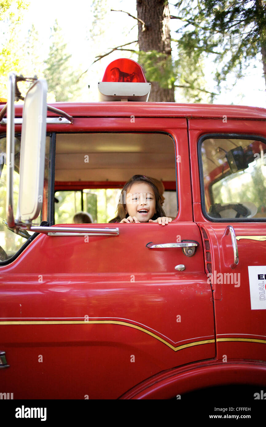 A young girl plays in a fire truck. - Stock Image