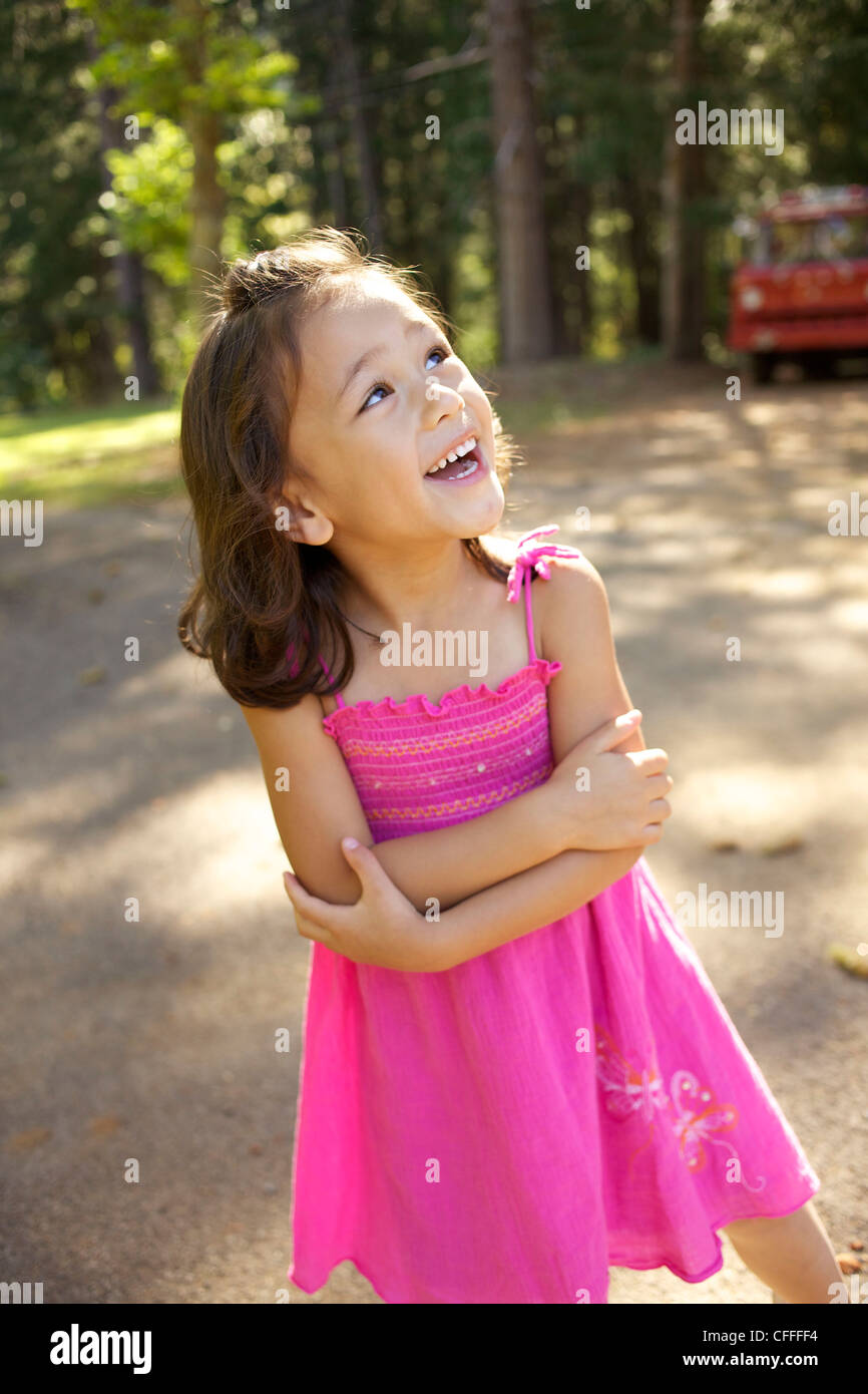 A young girl laughs in a pink dress. - Stock Image