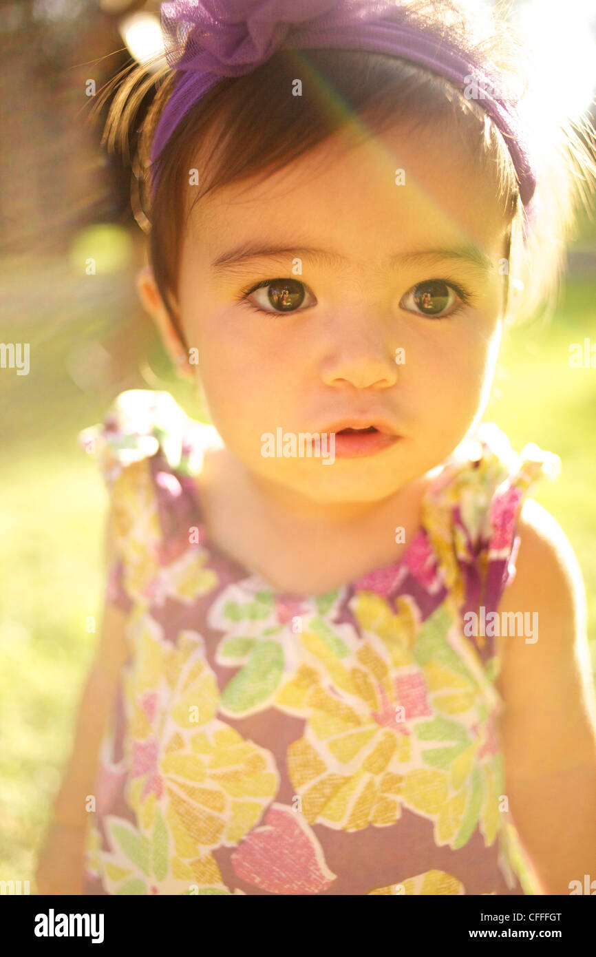 A little girl in a dress in the sun. - Stock Image