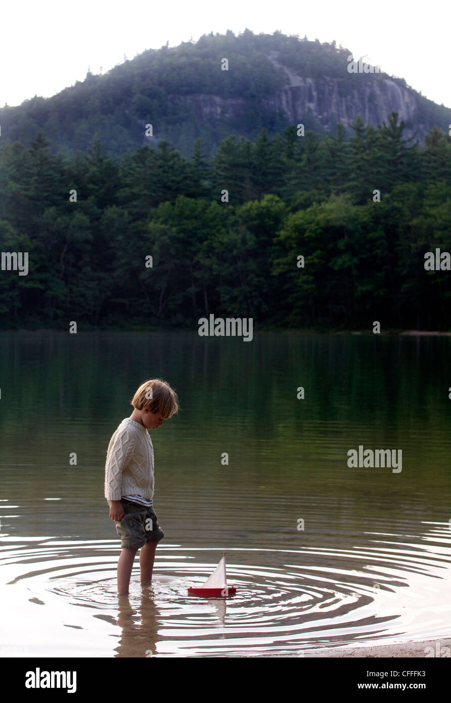 Six-year-old boy plays with a toy boat - Stock Image