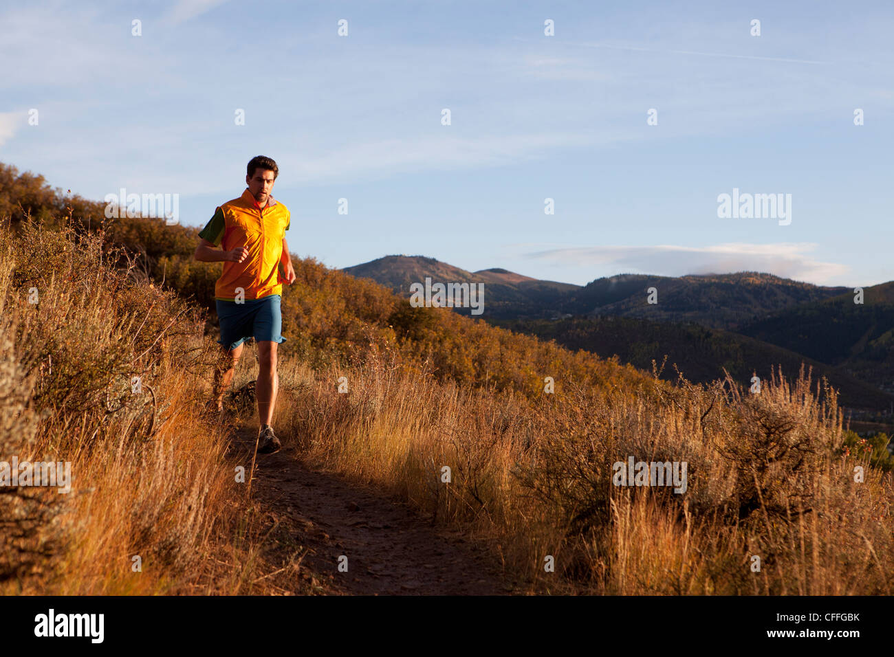 A man out for an early evening run. - Stock Image