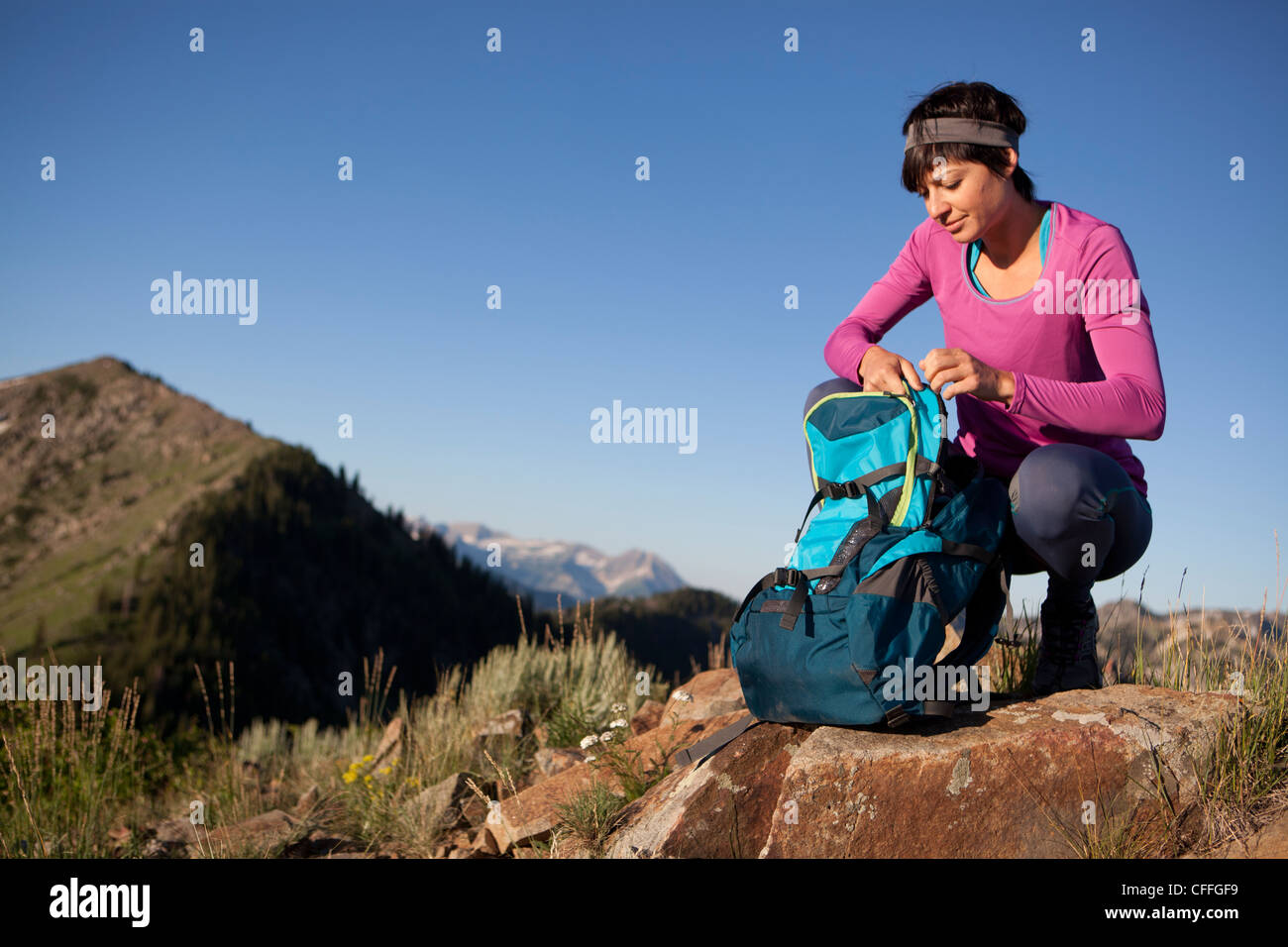 A woman pausing for a snack break on the Wasatch Crest Trail. - Stock Image