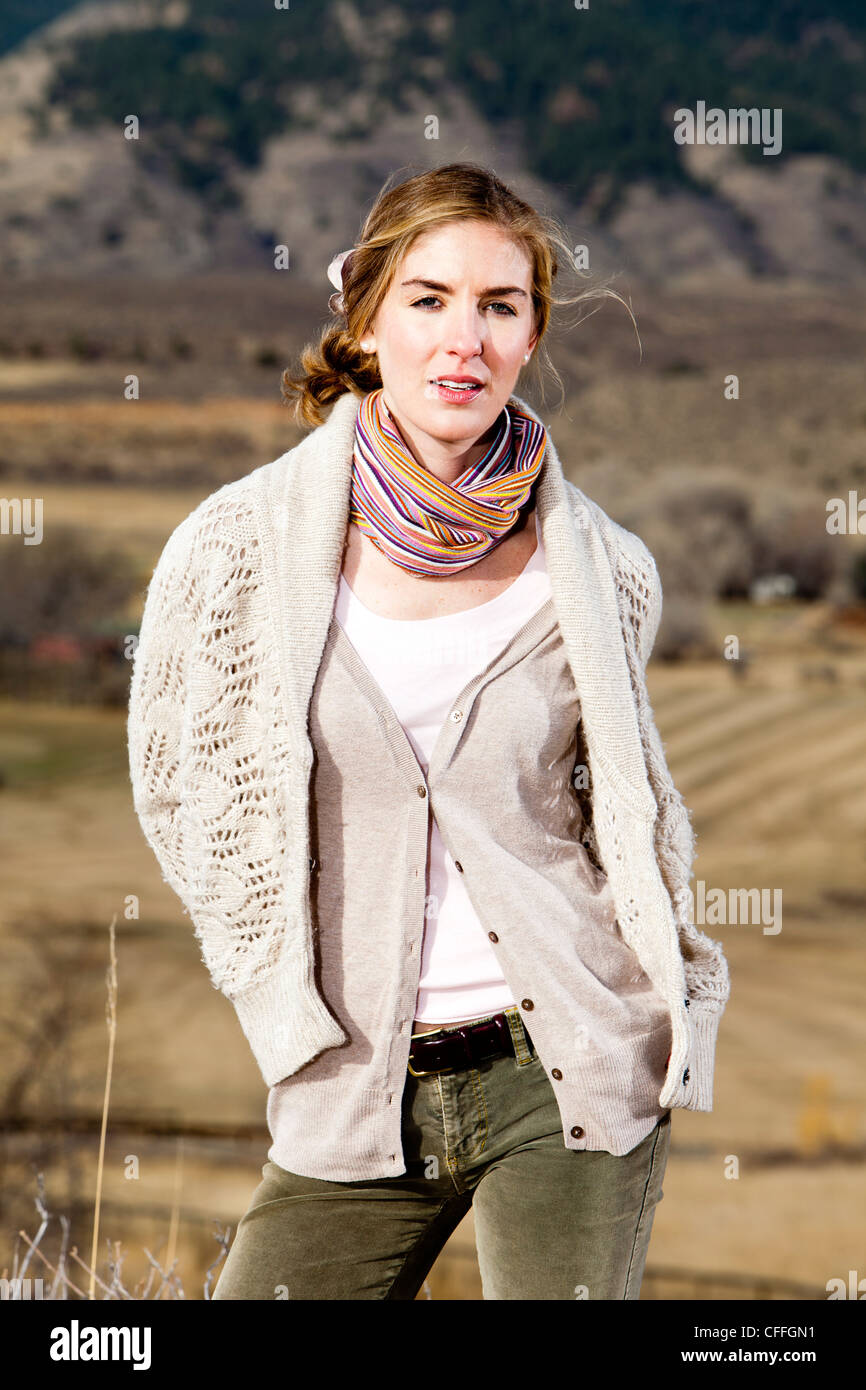 A young woman poses in layered outdoor clothing in Fort Collins, Colorado. - Stock Image