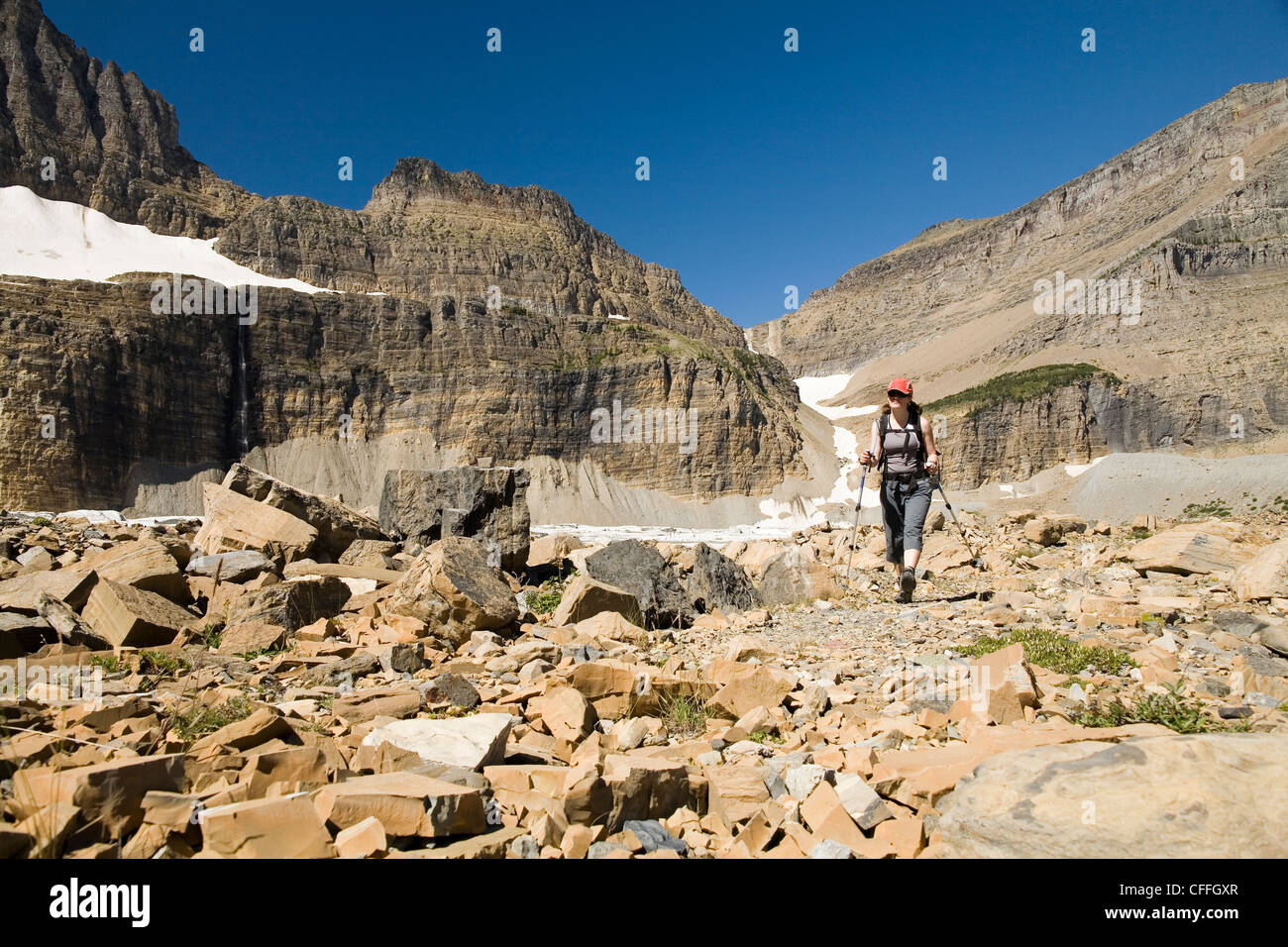 A woman in her early thirties hikes along the Grinnell Glacier trail in Glacier National Park, Montana. - Stock Image
