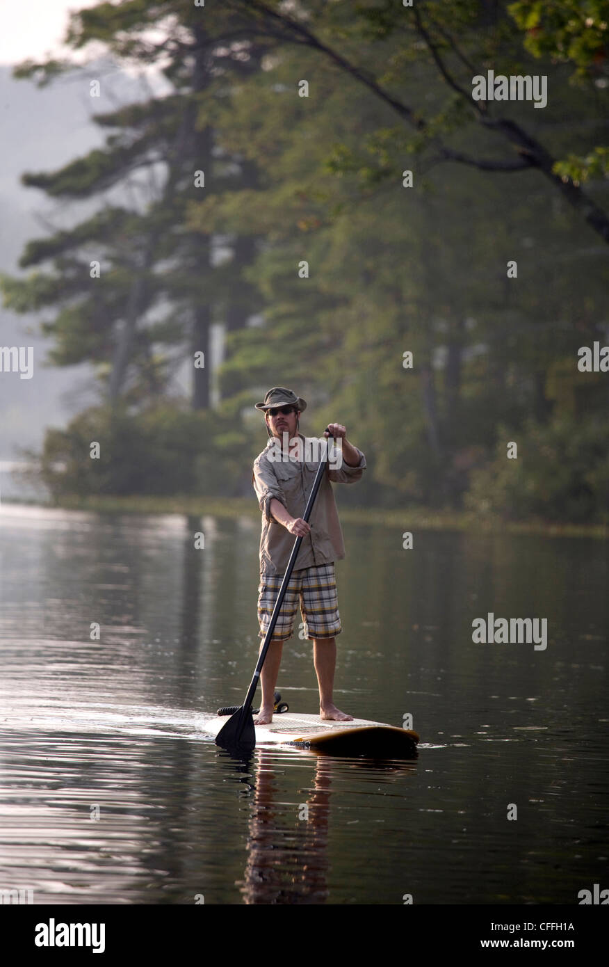 Man rides a SUP on Otter Lake in Greenfield, NH - Stock Image